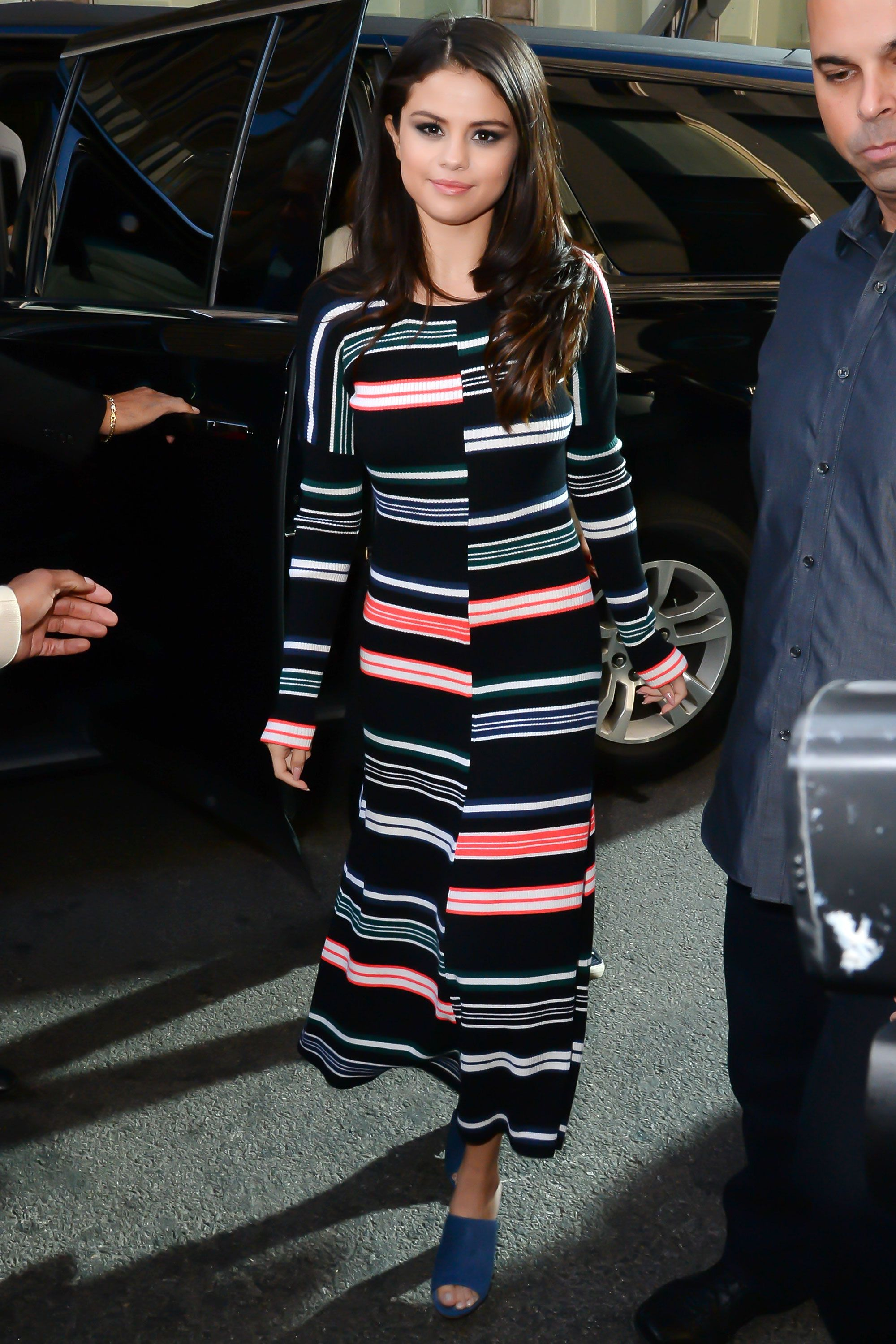 <p>Selena shows a sweater dress doesn't have to mean a neutral. Keep a graphic print the focal point with simple slides and minimal jewelry. </p>
