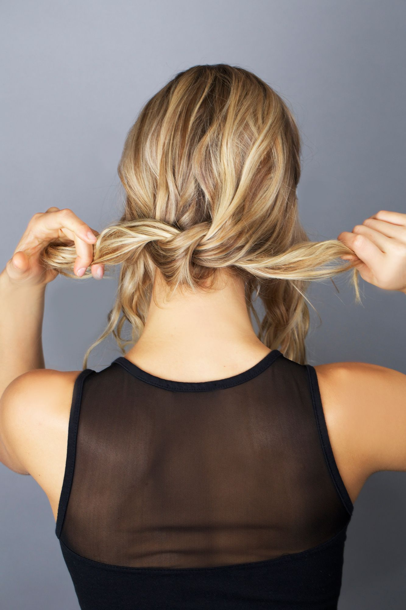 <p>Tie the two sections of hair behind your shoulders into a knot. </p>