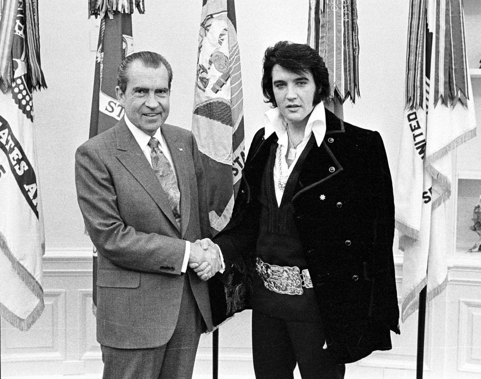 "Elvis Presley With Richard Nixon In 1970, Elvis appeared at the White House in a collar nearly as exaggerated as his belt and was named a ""Federal Agent at Large"" by President Nixon—he also received an honorary badge."