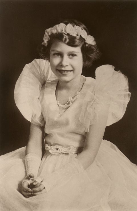 "<p>Looking every bit the princess she was, Elizabeth posed for a portrait at eight years old in a cute tulle-trimmed gown complete with a <a href=""http://www.goodhousekeeping.com/beauty/hair/g3374/flower-hairstyles-crowns/"" target=""_blank"">flower crown</a>. She even rocked an '80s trend in those fingerless lace gloves!</p>"
