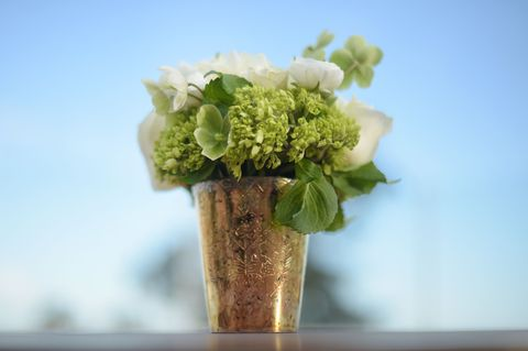 <p>A spring-themed party without flowers is like pizza without cheese. Just, <em>what is the point? </em>However, flowers can be expensive—especially when decorating a large space. Get more mileage out of your arrangements by creating small bouquets to scatter around the room instead of one larger floral focal point. (We picked green and white stems for an extra fresh feel.)</p>