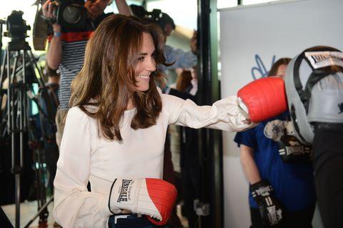 Boxing glove, Tripod, Boxing, Glove, Elbow, Boxing equipment, Camera accessory, Carmine, Camera, Sports gear,