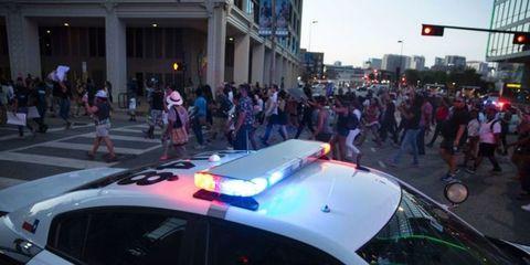 People, Crowd, Pink, Pedestrian, Luxury vehicle, Public event, Downtown, Audience, Mid-size car, Law enforcement,