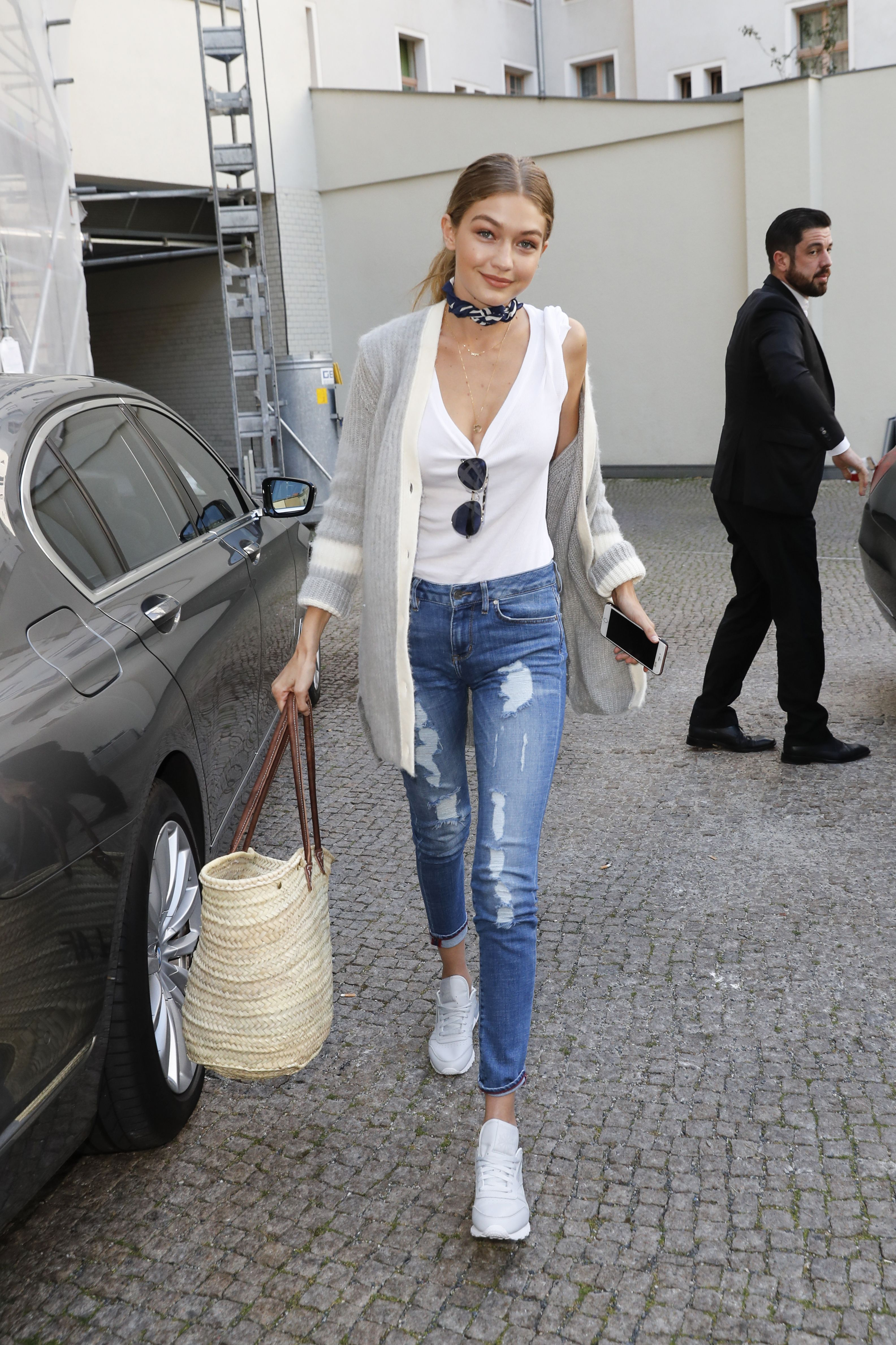 <p>Will a T-shirt and jeans never *not* be an ideal outfit? Here, she's added a cardigan and neckerchief—and a straw bag, because ~summer vibes~ are infinite. (And straw bags are still very, very hot at the moment.)</p>
