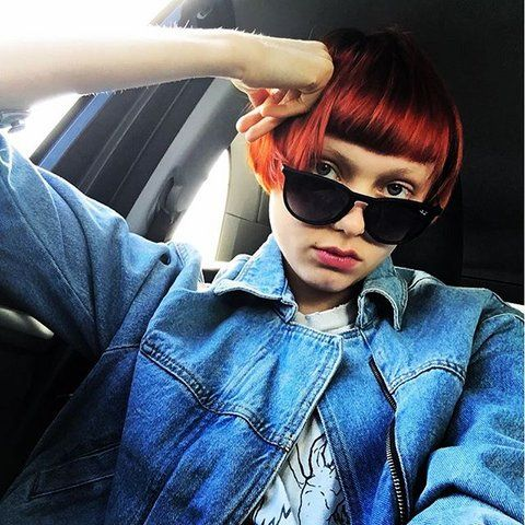 <p>Oozing cool-girl—we love the reddish pops of orange on her cropped, micro-banged 'do.</p>