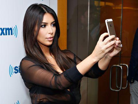 Shoulder, Hand, Mobile phone, Wrist, Eyelash, Portable communications device, Logo, Telephony, Long hair, Black hair,