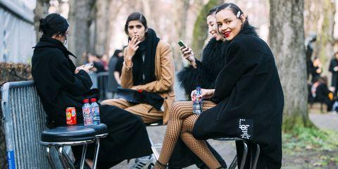 Footwear, Trousers, Outerwear, Winter, Coat, Jacket, Sitting, Street fashion, Conversation, Outdoor furniture,