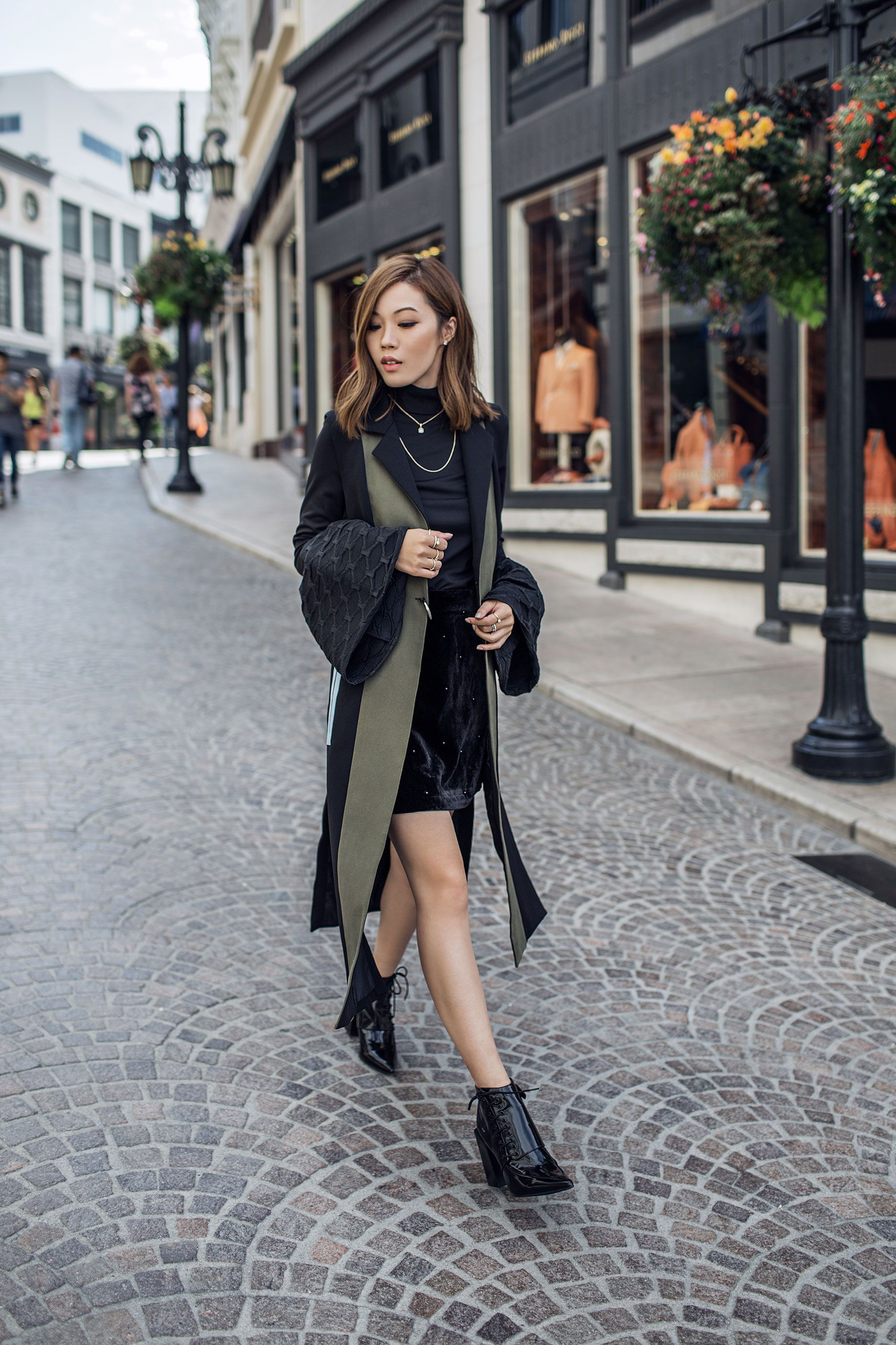 """<p>If you're into transitional dressing, go for an outfit that's a bit more dramatic, like this black-and olive-layered look. """"The exaggerated sleeves on the sweater elevate the entire look,"""" says Tsang. """"The velvet skirt and layered [14k] gold necklaces make it even more glamorous, and the long green vest and patent leather booties gives it an edgy feel.""""</p><p><em data-redactor-tag=""""em"""">Asilio Vest and Top&#x3B; C/Meo Collective Skirt&#x3B; Senso Boots&#x3B; PANDORA Jewelry Necklaces, price varies, <a href=""""http://estore-us.pandora.net/en-us/necklaces/?cid=BrndMedia_Drop6_Dec_2016_MarieClaire_CustomContent_NativeInfluenceArticles_Necklaces_Collection"""" target=""""_blank"""" data-tracking-id=""""recirc-text-link"""">pandora.net</a></em></p>"""
