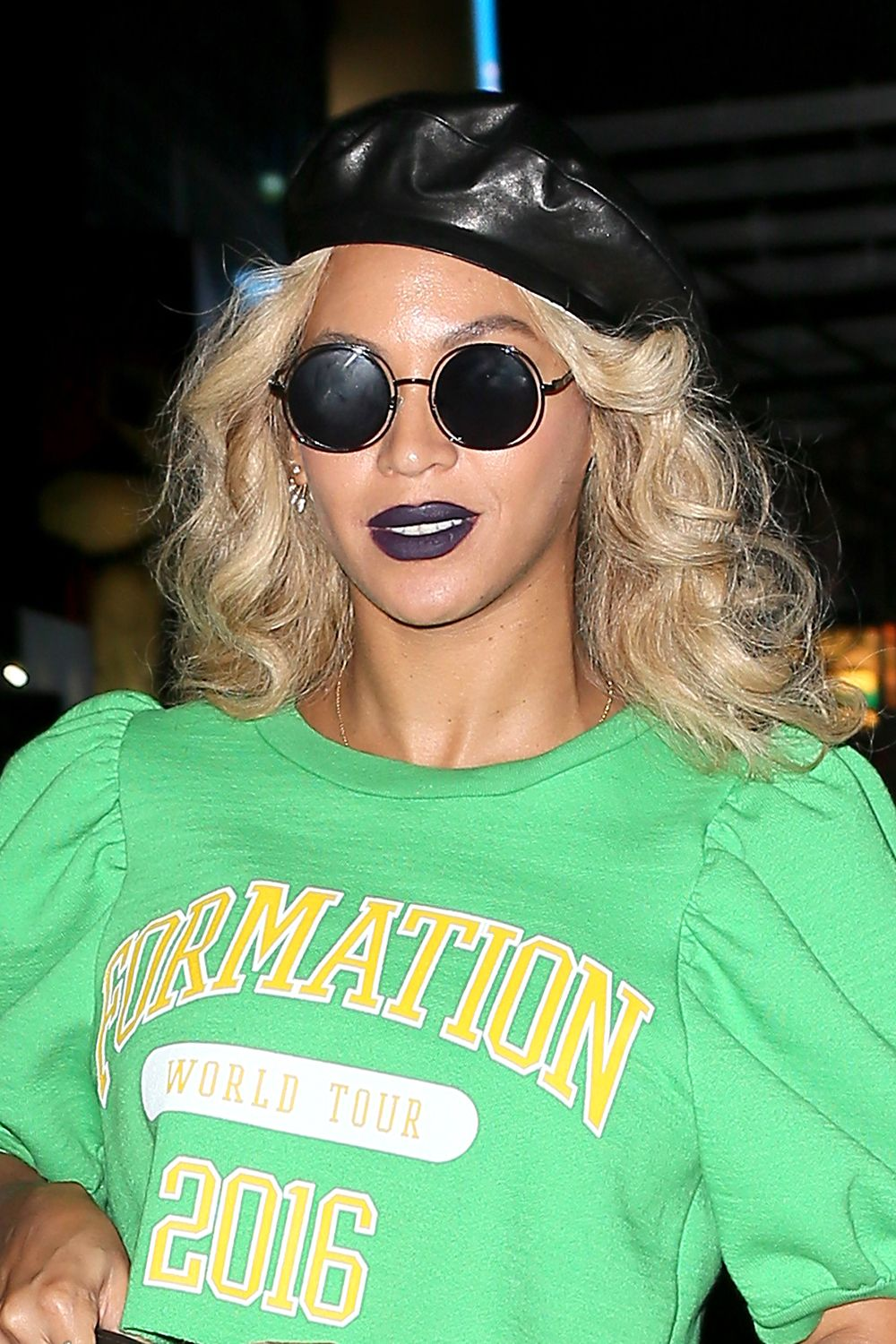 <p>Queen Bey punctuates her look with a leather beret, round black sunglasses, and a vampy blue-tinged lip.</p>