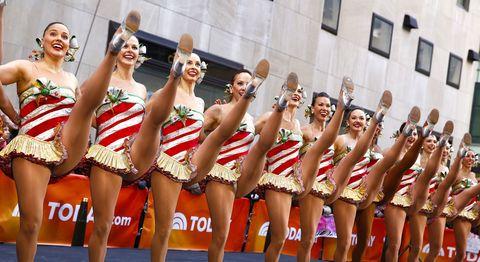 Smile, Performing arts, Human leg, Entertainment, Team, Cheerleading uniform, Headgear, Dancer, Thigh, Performance,