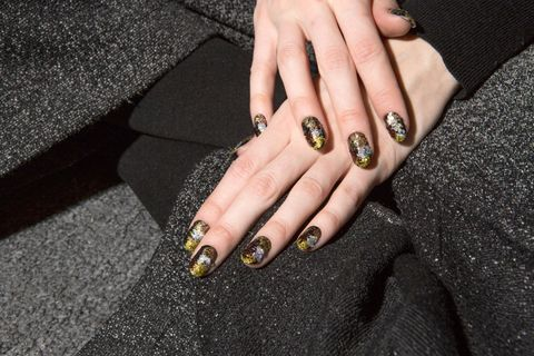 """<p>Celebrity nail artist<a class=""""body-el-link standard-body-el-link"""" href=""""https://www.instagram.com/ginaedwards_/?hl=en"""" target=""""_blank"""" data-tracking-id=""""recirc-text-link"""">Gina Edwards</a>dreamed up Naeem Khan's <a href=""""http://www.marieclaire.com/beauty/news/a25430/mosaic-nails-trend/"""" target=""""_blank"""" data-tracking-id=""""recirc-text-link"""">mosaic nail look</a> by applying loose silver, gold, and bronze glitter to<a class=""""body-el-link standard-body-el-link"""" href=""""http://bit.ly/2kyDv3G"""" target=""""_blank"""" data-tracking-id=""""recirc-text-link"""">KISS' imPress Press-on Mani pre-glued black nails</a><span class=""""redactor-invisible-space"""" data-verified=""""redactor"""" data-redactor-tag=""""span"""" data-redactor-class=""""redactor-invisible-space""""> with a small flat brush. The secret to making the shiny stuff stick? Clear nail polish.</span><span class=""""redactor-invisible-space"""" data-verified=""""redactor"""" data-redactor-tag=""""span"""" data-redactor-class=""""redactor-invisible-space""""></span></p>"""