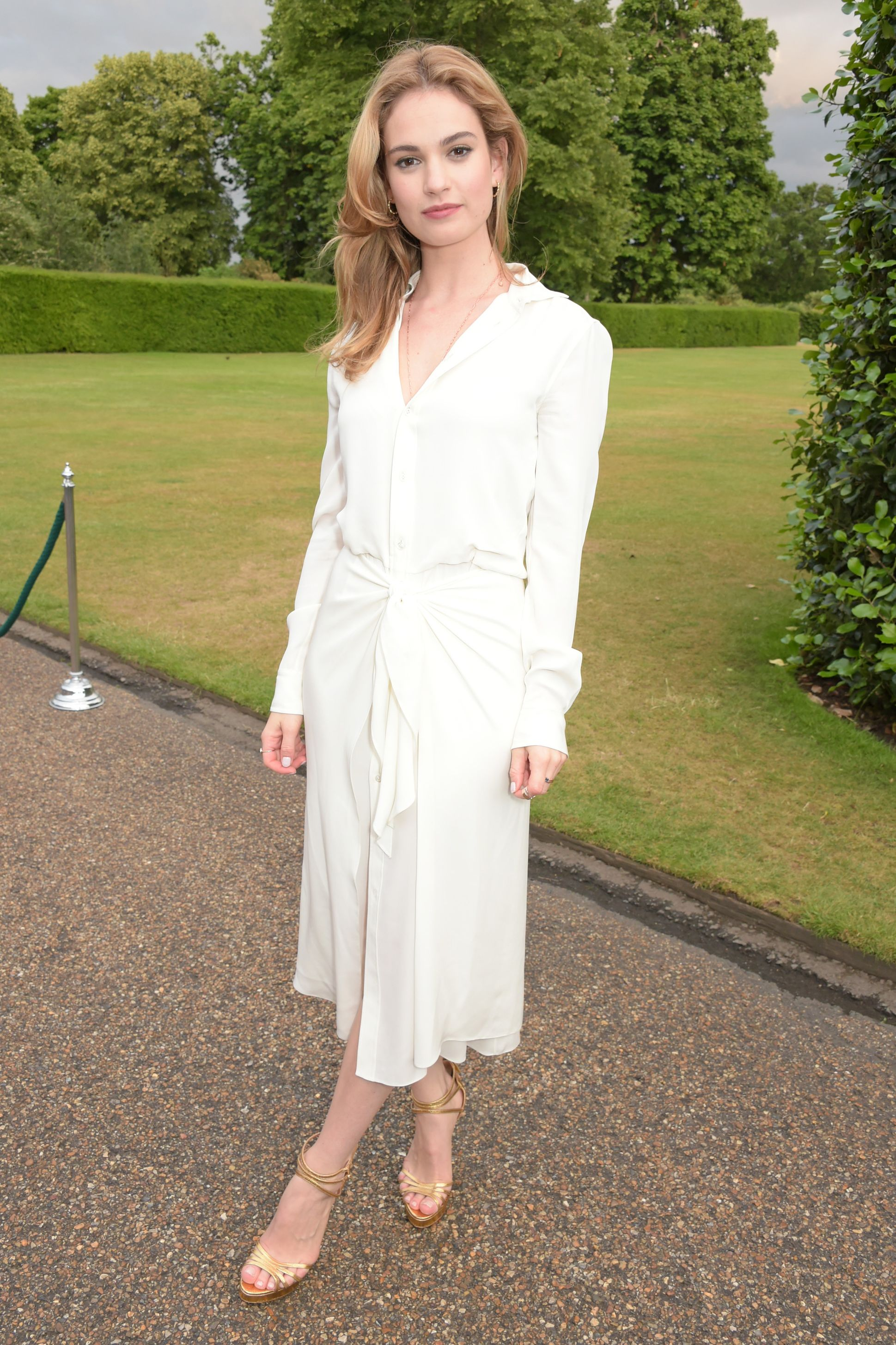 Lily James If you're heading to a fussier Memorial Day party, throw on a dressy shirt-dress and heels that you don't mind getting stuck in the grass.
