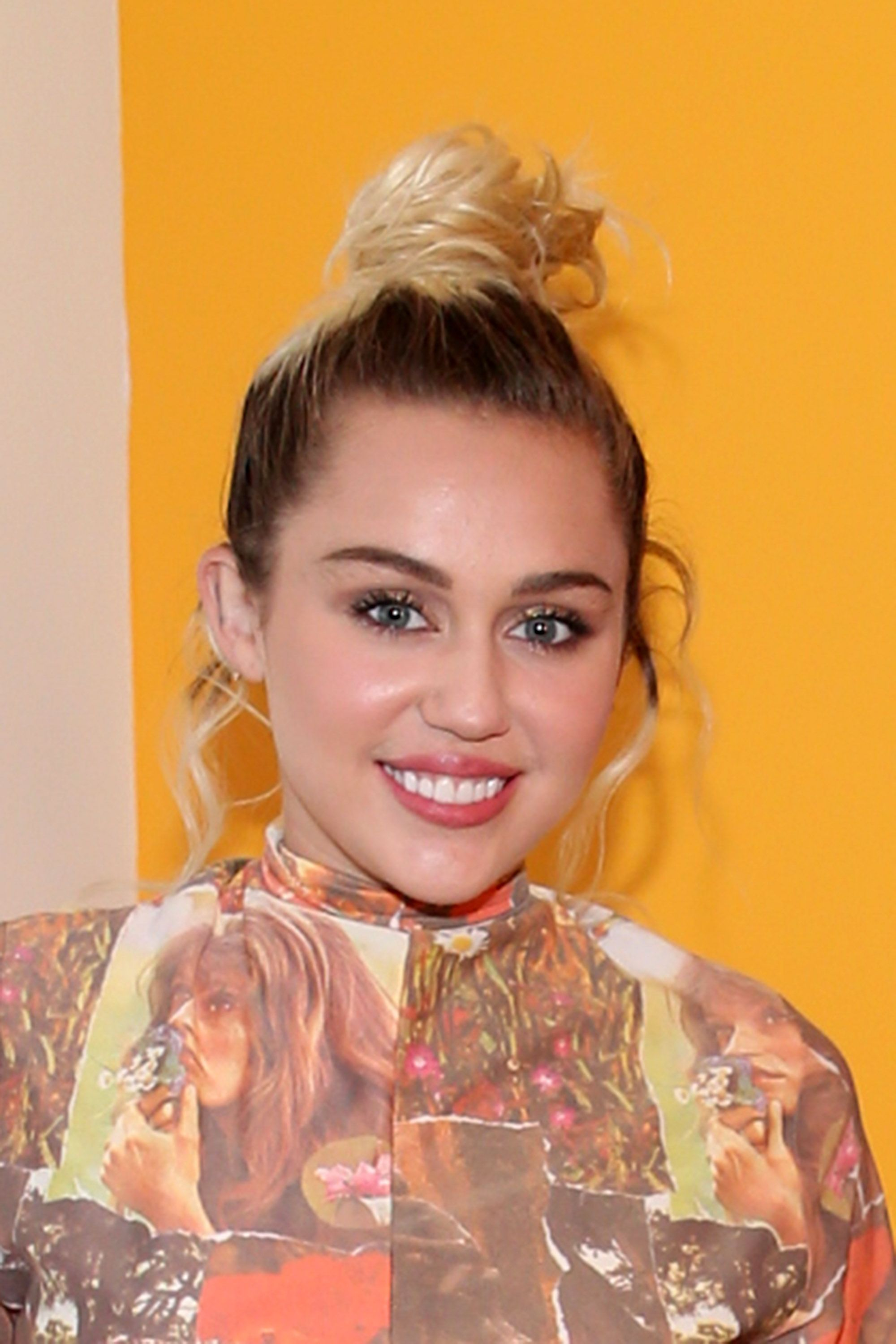 <p>Miley knows: A topknot gives you more of a neck when your collar is high. Some tendrils sweeten the deal. </p>