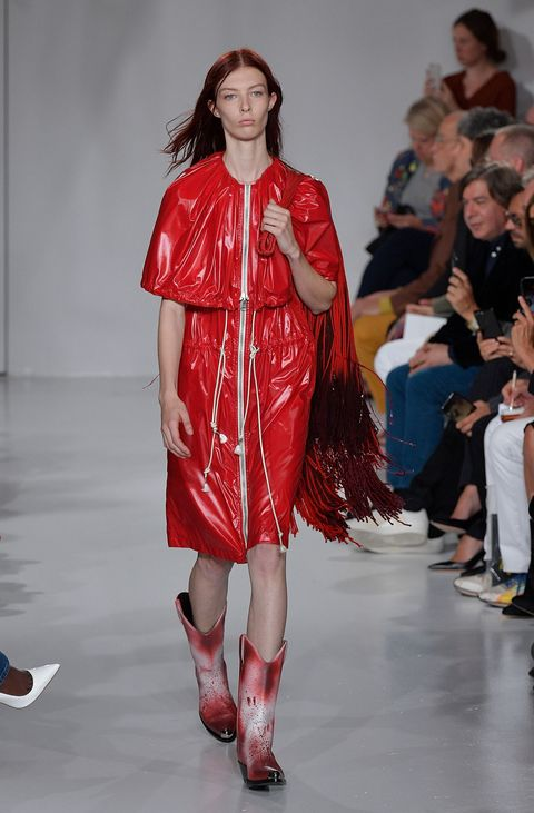 "<p>And at Calvin Klein, the cowboy boot's normalizing power. Here, with a rubbery dress, they bring Raf Simons' American horror story down to earth.</p><p><em data-redactor-tag=""em"" data-verified=""redactor"">Shop similar: Calvin Klein, $1,295</em></p><p><strong data-redactor-tag=""strong"" data-verified=""redactor"">BUY IT: <a href=""https://www.barneys.com/product/calvin-klein-205w39nyc-spazzolato-leather-cowboy-boots-505368757.html"" target=""_blank"" data-tracking-id=""recirc-text-link"">barneys.com</a>.</strong></p>"