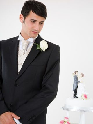 groom looking at a wedding cake