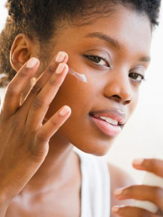 black woman applying eye cream