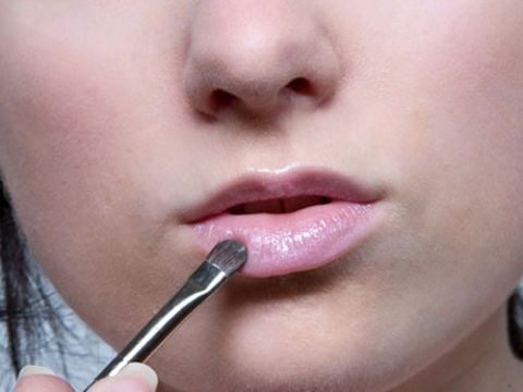 woman applying lip gloss with a lip brush