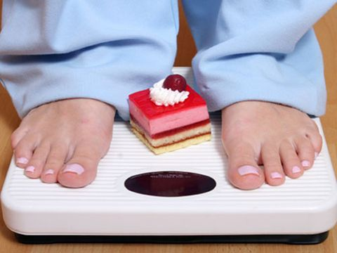 feet on scale with cake between feet