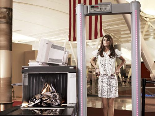 model in black and white dress going through airport metal detector