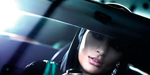 woman driving wearing two big drings and large bangle