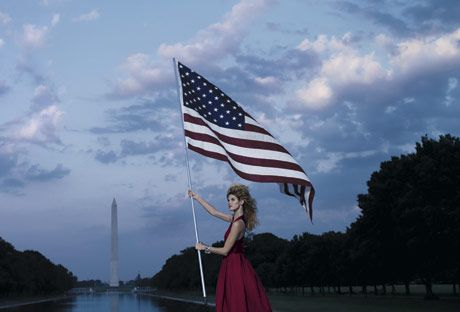 model in cherry red gown holding american flag