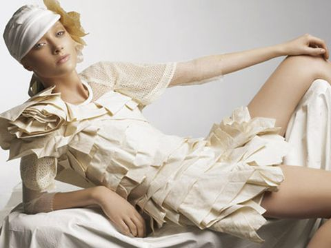 model in white cap and cream colored ruffled dress