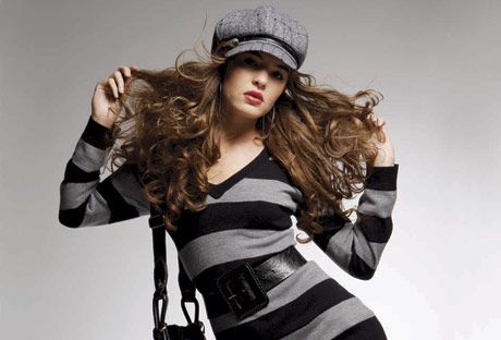 model in striped black and gray sweater and gray knee length shorts