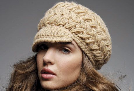 model wearing a cream colored chunky knit hat