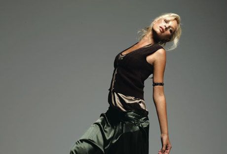 model wearing a black vest over a satin cami and long skirt