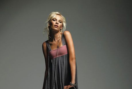 model wearing a sleeveless gray dress over black tights