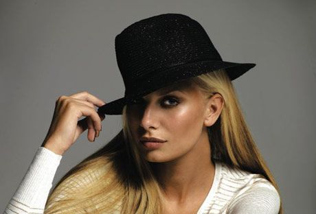 model in a white knit top and black fedora