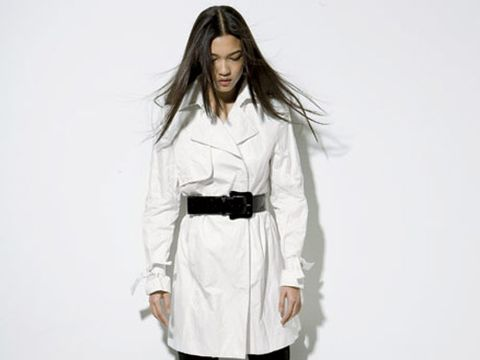 model in black leggings and a white trench cinched with a black belt
