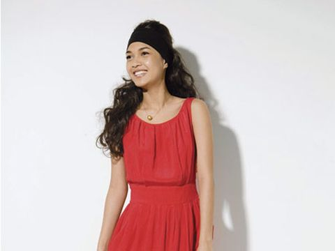 model wearing a red loose dress and black fabric wrap on head