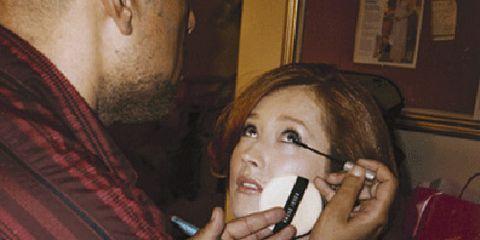woman having mascara applied by stylist