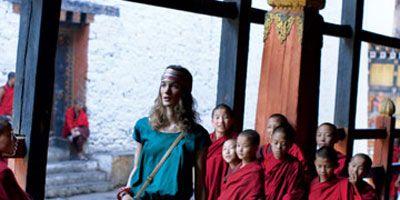 model in blue dress with monks in bhutan