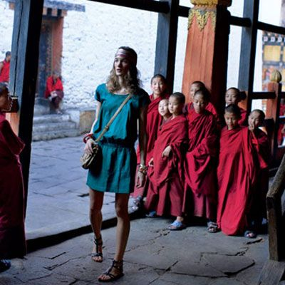 model in blue dress with monks in bhutan