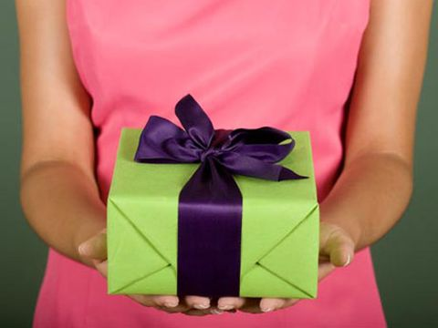 woman in pink dress holding gift wrapped in green with purple ribbon