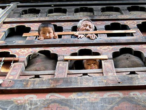 residents looking out windows at a fashion photo shoot in bhutan
