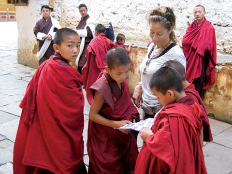 monks in training in bhutan looking at polaroids