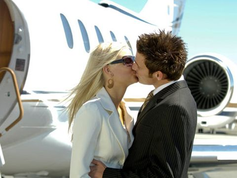 man and woman kissing beside an airplane