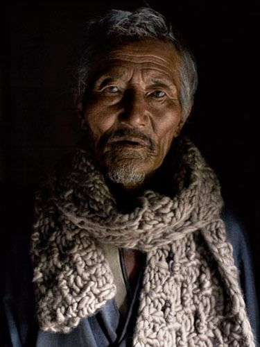 gray haired man in scarf