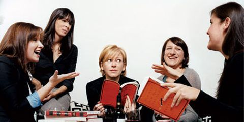 women around a table full of books