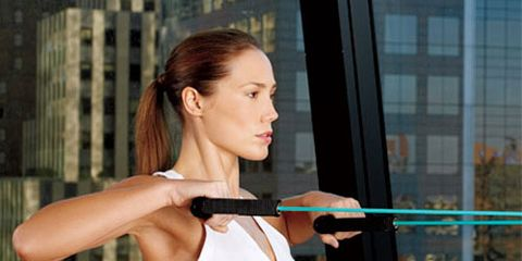 woman working out in front of window with view of city