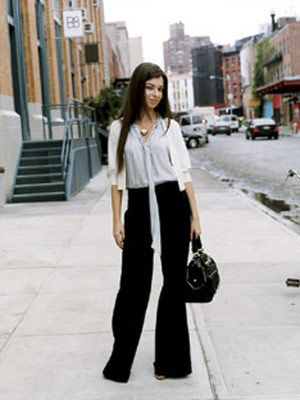 woman on city sidewalk in generra top and high waisted black pants from french connection