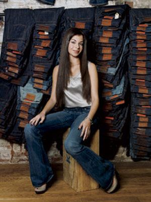 woman in jeans sitting in front of stacks of jeans