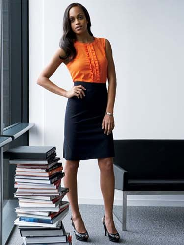 woman standing in office next to stack of books in orange shirt and black skirt