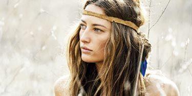 woman sitting in field in hippie clothing