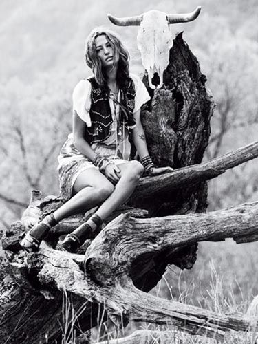 black and white image of woman sitting outside on a dead tree stump with a cow skull behind her