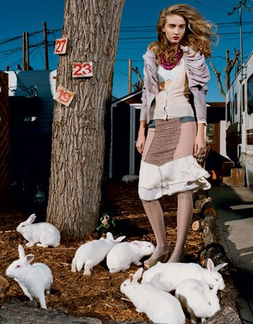 disheveled looking model standing under a tree in a trailer park surrounded by white rabbits