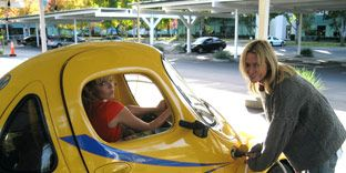 woman pumping recharging a yellow electric car on the google campus